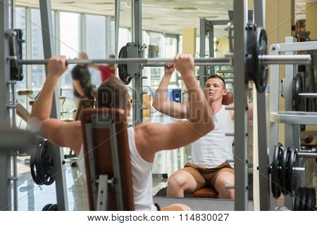 Young bodybuilder lifts weights.