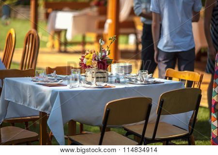 Decorated Table With Flowers In The Garden