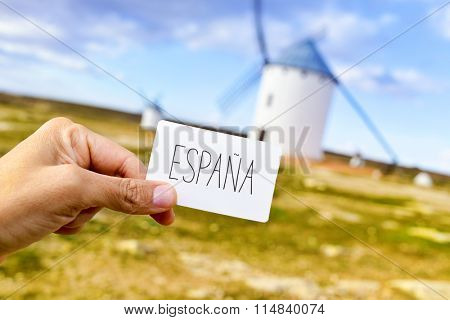 closeup of the hand of a young man showing a signboard with the word Espana, Spain in Spanish, in Campo de Criptana, Spain, with some traditional white windmills in the background