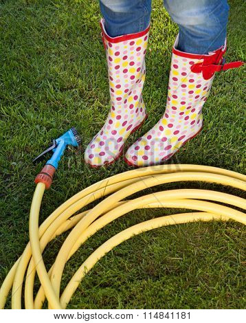 Woman wearing colorful wellies with garden water hose