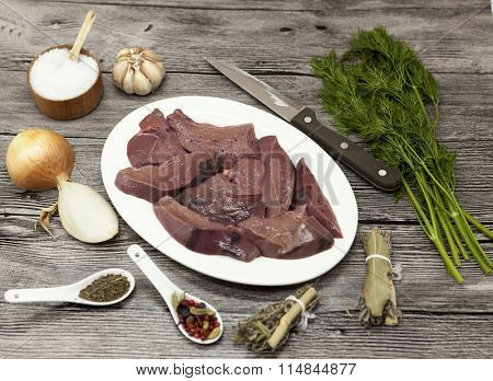 Pieces of fresh raw beef liver, onion, garlic, spices, dill, parsley, salt, knife, olive oil on porcelain plate on a wooden background