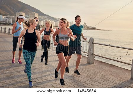 Group Of Athletes Running Along A Seaside Promenade
