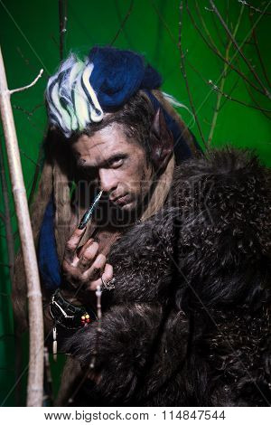 Portrait Muscular Werewolf With Dreadlocks With Long Nails Among The Branches Of The Tree