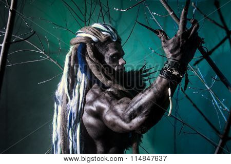 Portrait Muscular Werewolf With Dreadlocks Among The Branches Of The Tree
