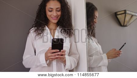 Charming Young Female Brunette Model Texting In Front Of Mirror