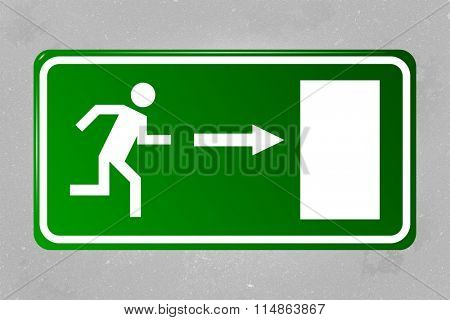 Emergency exit sign hanging on a concrete wall