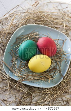 Easter Eggs In Straw Plate On A White Background
