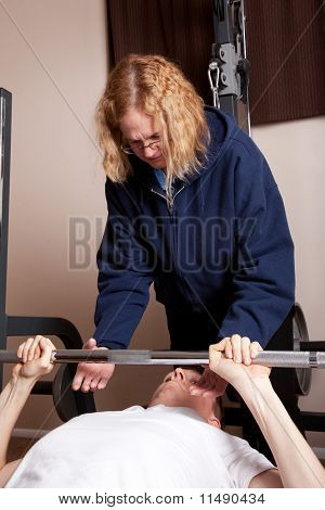 Mother spots son on bench press