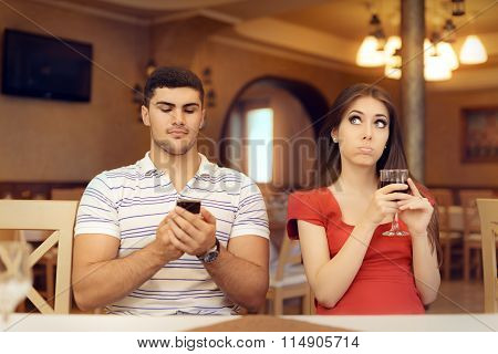 Bored Girl in a Date with Her Boyfriend Addicted to his Smartphone