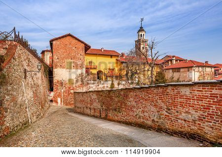 Cobbled street, red brick wall and colorful houses in old town of Saluzzo in Piedmont, Northern Italy.