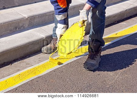 Painting of a yellow stripe parking, on the ground (France).  Works for the regularization of parkin