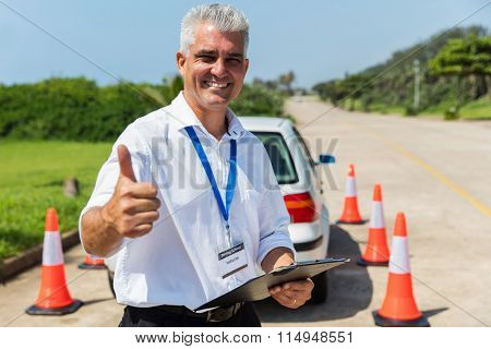 cheerful driving school instructor thumb up