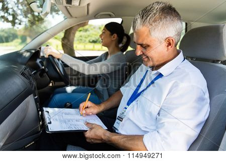 handsome senior driving instructor testing learner driver