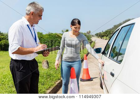 confident female learner driver with instructor doing pre driving inspection
