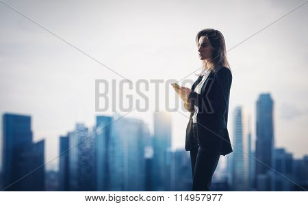 Young woman wearing modern suit holding her smartphone in a hands. City on the background