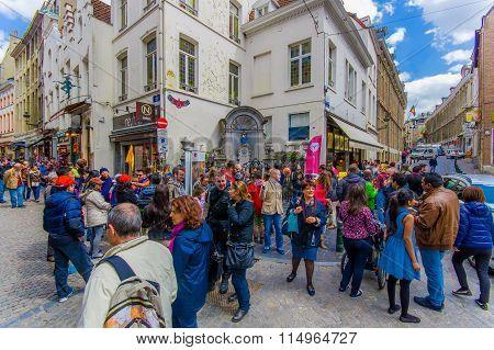 BRUSSELS, BELGIUM - 11 AUGUST, 2015: Crowd of tourists watching Manneken Pis famous landmark bronze