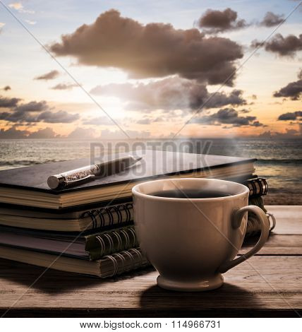 Hot Coffee With Notebooks And Pen On Wooden Table With View Of The Sea