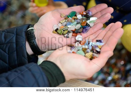 Colored stones in his hands.