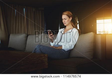 Young female searching information on mobile phone while relaxing in modern coffee shop