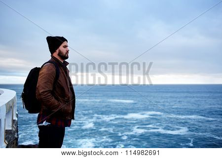 Hipster guy standing on the rock against blue sea background with copy space for your text area