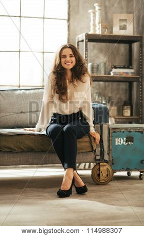 Smiling Brunet Woman In Elegant Clothing Sitting In Loft Room