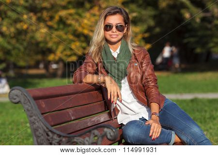 Beautiful young blond woman sitting on a bench in a park