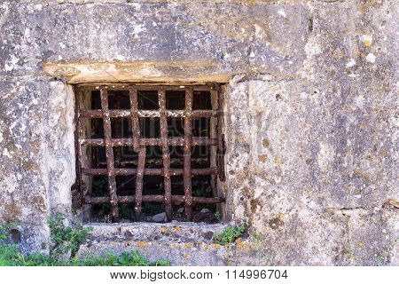 Old Window With A Rusty Grating On Ancient Wall