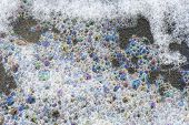 Colorful foam and bubbles induced by pollution in sea water on beach poster