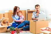 The happy family with laptop at repair and relocation on a background of boxes poster