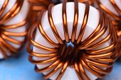 Macro of a copper coils on blue background poster