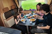 Family eating together in RV interior, travel in motorhome (camper, caravan) on vacation poster