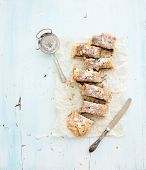 Homemade apple and almond strudel on baking paper over light blue wooden backdrop, top view poster