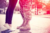 Young military couple kissing each other homecoming concept soft focus cross process toning applied light leak in the corner poster