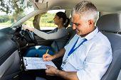 handsome senior driving instructor testing learner driver poster