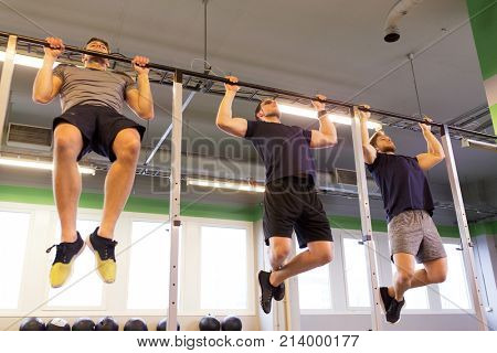 sport, fitness, exercising and people concept - group of young men doing pull-ups on horizontal bar in gym
