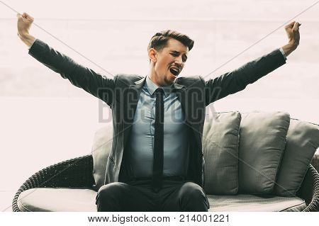 Portrait of tired young man wearing suit, sitting on couch in cafe, yawning, raising hands