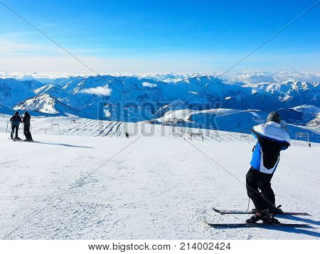 Les Deux Alpes, France - December 30, 2012: Ski resort slopes, skier making photo, mountain panorama in France, French Alps