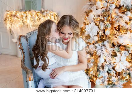 Happy family mother and daughter near a Christmas tree on Christmas eve at home. Woman and little girl relax in a white bedroom near the Christmas tree. Family at home. Young mother playing whith her daughter