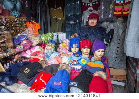 OLGIY, BAYAN-OLGIY, MONGOLIA - SEP 27, 2017: Unknown woman in the city market sells winter hats. In Bayan-Olgiy province is populated to 88,7% by Kazakhs.
