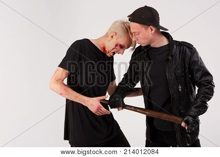 Two young guys in black are fighting. The guy in the cap beats a wooden bat in the stomach to another guy. Isolation.