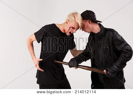 A dangerous guy in a black cap beats a defenseless guy with a battered face and bruises with a wooden bat. Isolation.
