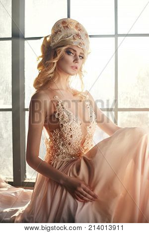 Fairy With Long Blonde Hair In Light Is On Background Of A Large Window, Art Fashion Girl. Beautiful