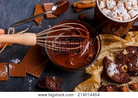 Hand hampered with a halter melted chocolate with hazelnuts. A cup of marshmallow in chocolate, a cupcake with nuts, cinnamon sticks and prisapona sugar powder close-up