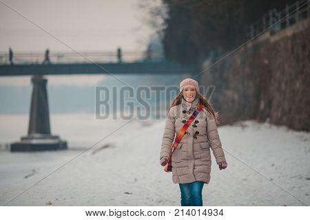 Warmly dressed girl walking on the frozen river in winter
