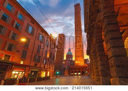 Two Towers, Asinelli and Garisenda, both of them leaning, symbol of Bologna, statue of San Petronius and Church of Saints Bartholomew and Gaetano at sunrise, Bologna, Emilia-Romagna, Italy