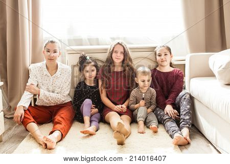 Happy big family of brothers and sisters sitting on the floor