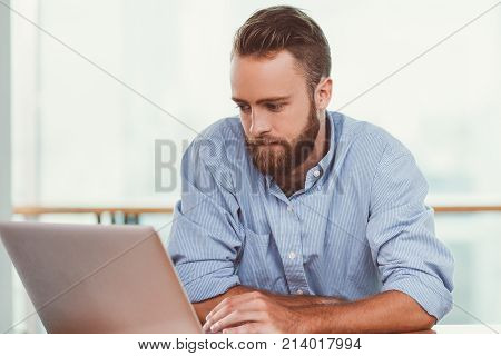 Closeup portrait of focused young man working on laptop computer and sitting at cafe table with blurred railing in background. Front view.