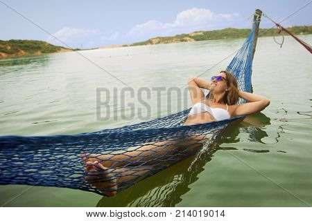 Feeling at home away from home - Brazilian woman on the hammock in water - Brazil Fortaleza Cumbuco