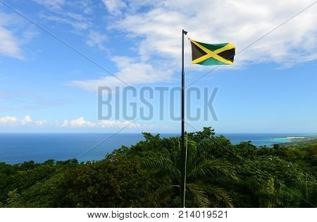 Flag of Jamaica waving against blue sky. Flag of Jamaica have a gold saltire on a green and black field.