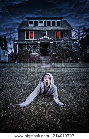 Terrified boy yelling and trying to escape from a haunted house